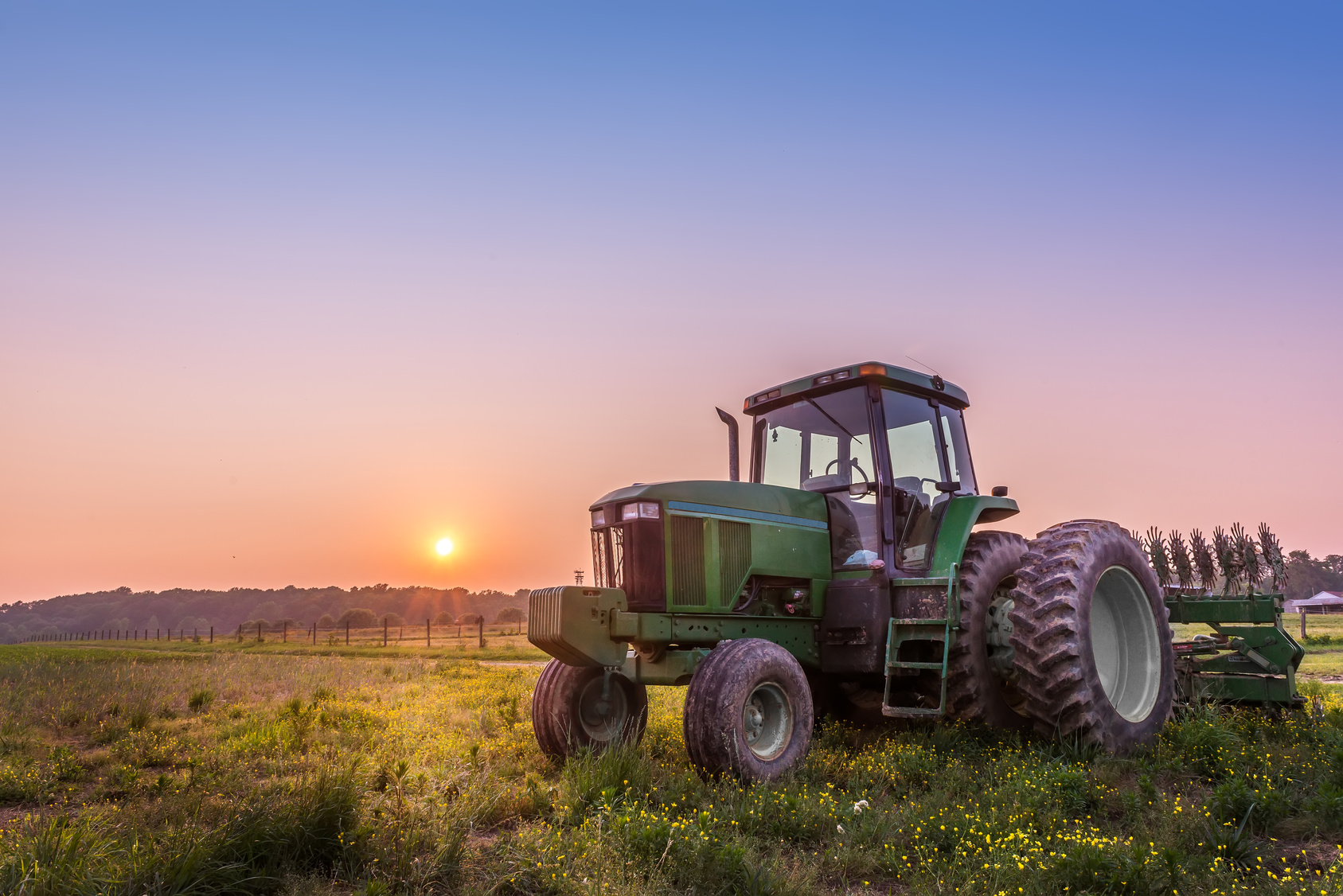 empty farm tractor in field with sun setting in background