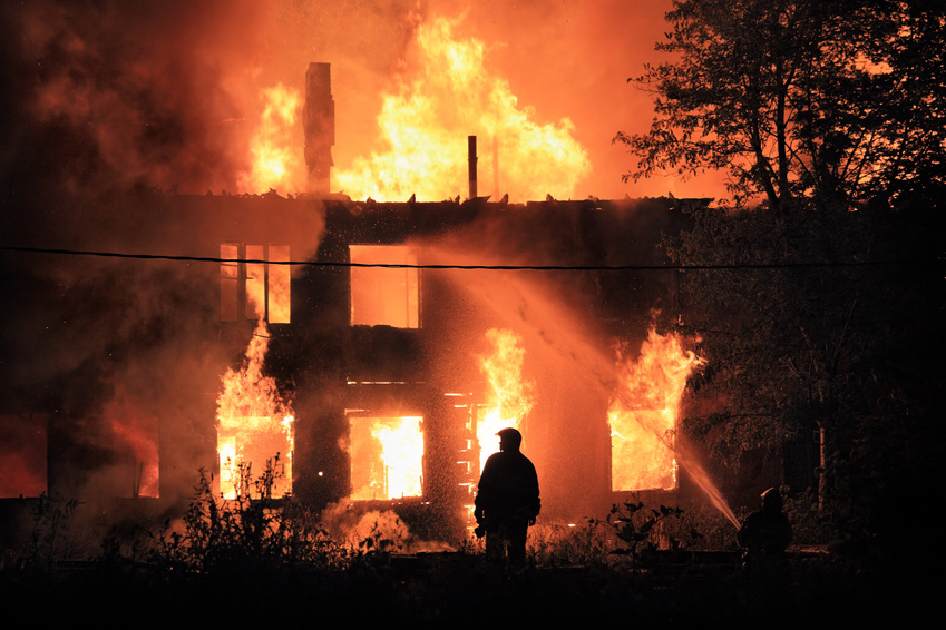 house on fire, fireman silhouette with water coming from hose
