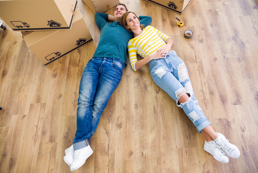 happy couple laying on floor with empty boxes